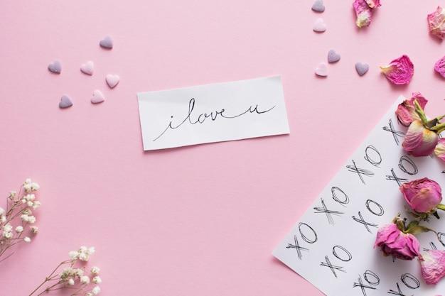 Papier z tytułu w pobliżu ornament serca i zestaw kwiatów