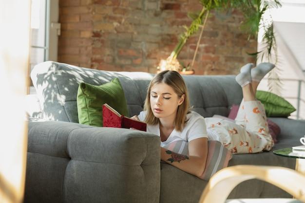 Papierkowa robota. kaukaska kobieta, freelancer podczas pracy w domowym biurze podczas kwarantanny. młoda kobieta w domu, samodzielnie na białym tle. korzystanie z gadżetów. praca zdalna, zapobieganie rozprzestrzenianiu się koronawirusa.