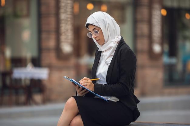 Papierkowa robota. piękny portret muzułmańskiej bizneswoman sukcesu, pewny siebie szczęśliwy ceo, lider, szef lub menedżer. korzystanie z urządzeń, gadżetów, praca w podróży wygląda na zajętą. uroczy. inkluzywna, różnorodność.