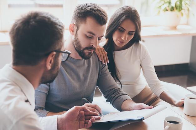 Papierkowa robota przed rozdaniem. pewny siebie młody mężczyzna podpisujący jakiś dokument, siedząc razem z żoną i mężczyzną w koszuli i krawacie
