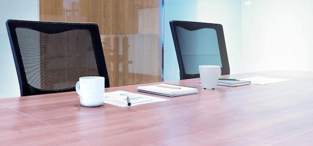 Papierkowa robota z filiżanką kawy i notatnik na stole z dwoma czarnymi fotelami w sali konferencyjnej