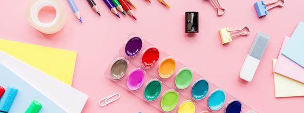 Papiernicze artykuły szkolne, ołówki, farby, papier na różowym tle