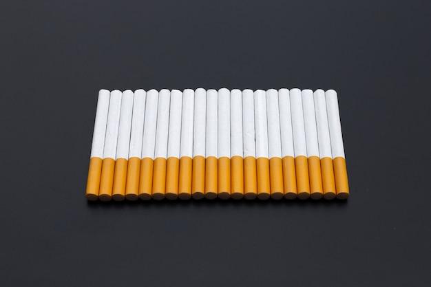 Papieros na ciemnym tle. zakaz palenia dla koncepcji zdrowia
