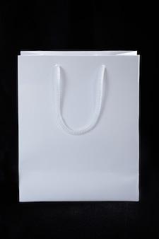 Papierowa biała torba na czarnym tle. produkty promocyjne. układanie logo