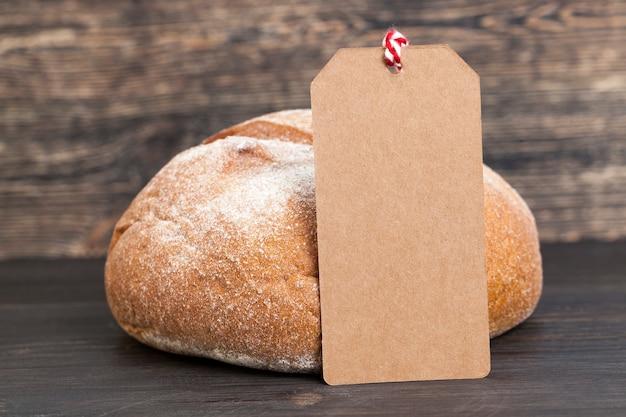 Papierowa brązowa etykieta na desce obok świeżego bochenka chleba pszennego z dodatkiem mąki żytniej, zbliżenie