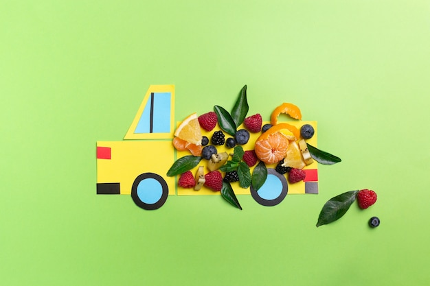 Papierowa ciężarówka rzemieślnicza z jagodami i owocami na zielono koncepcja żywności dla dzieci widok z góry płaska leżała wysokiej jakości zdjęcie