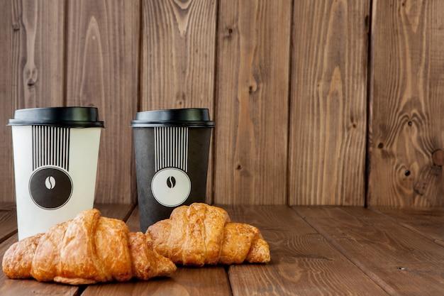 Papierowa filiżanka i croissants na drewnianym tle