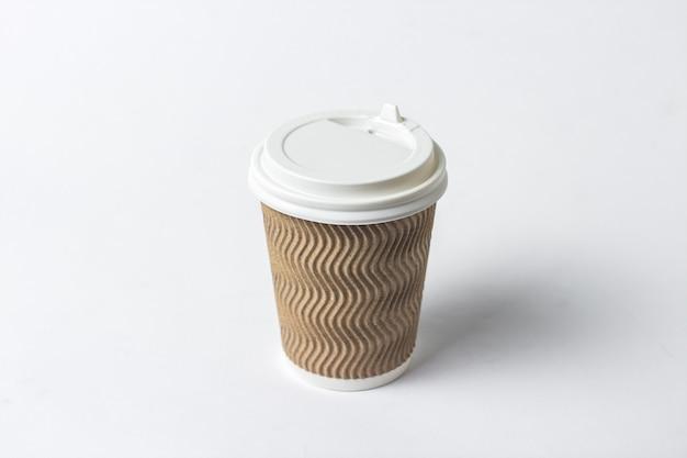 Papierowa filiżanka z ochronnym deklem na białym tle. koncepcja kawy lub herbaty na wynos, fast food, poranna kawa, śniadanie.