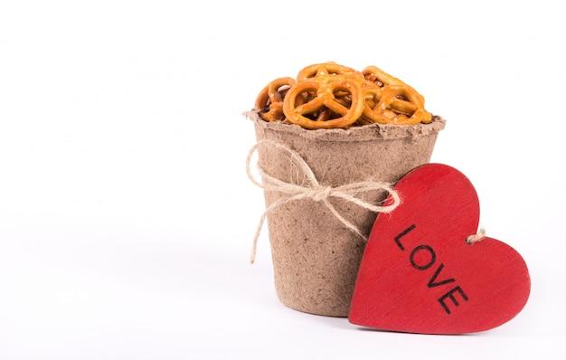 Papierowa filiżanka z słonymi krakers i czerwonym drewnianym sercem na białym tle.