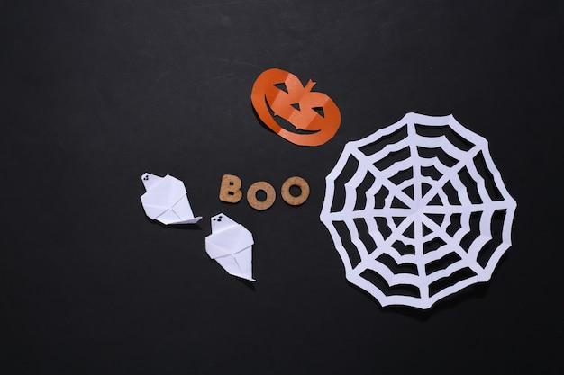 Papierowa głowa dyni halloween, duch, pajęczyna i słowo boo na czarnym tle. motyw halloween