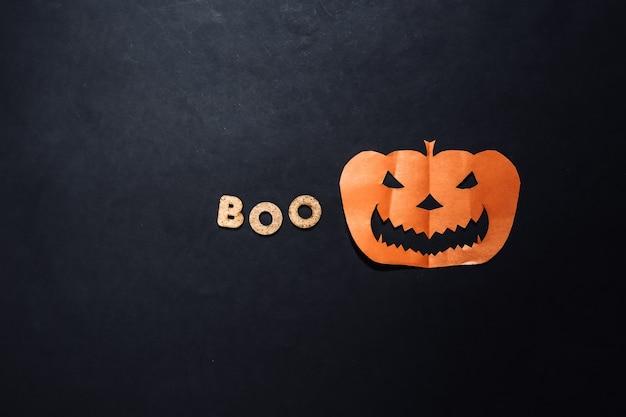 Papierowa głowa dyni halloween i słowo boo na czarnym tle. motyw halloween