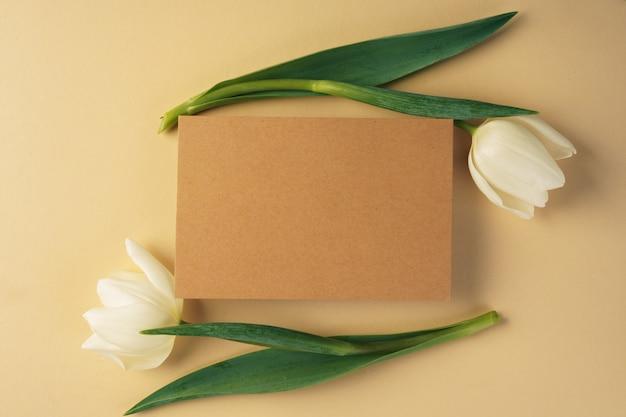 Papierowa karta rzemieślnicza otoczona świeżymi tulipanami na beżu