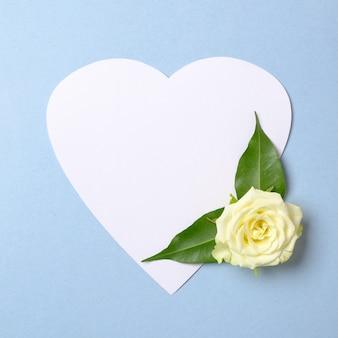 Papierowa karta w kształcie serca z białymi różami na pastelowym niebieskim tle