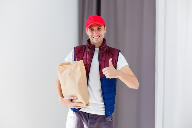 Papierowa kieszeń i pojemniki na żywność w rękach uśmiechniętego doręczyciela. jakość obsługi restauracji.