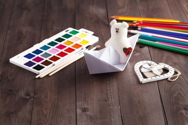 Papierowa łódź i miękka zabawka na drewnianym stole