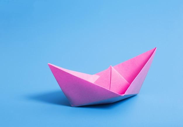 Papierowa łódź na błękitnego papieru ścianie