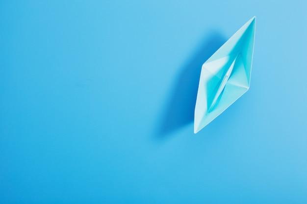 Papierowa łódź na błękitnego papieru tle