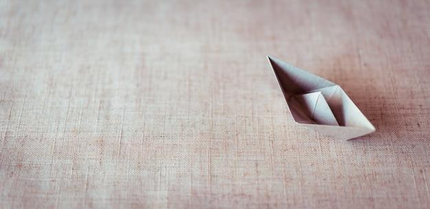 Papierowa łódź na brezentowym tekstury tle z kopii przestrzenią