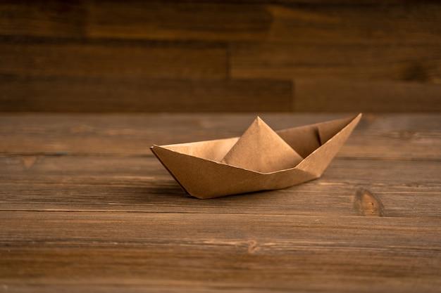 Papierowa łódź na drewnianym tle