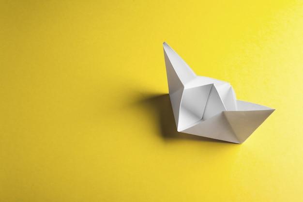 Papierowa łódź na żółtej powierzchni