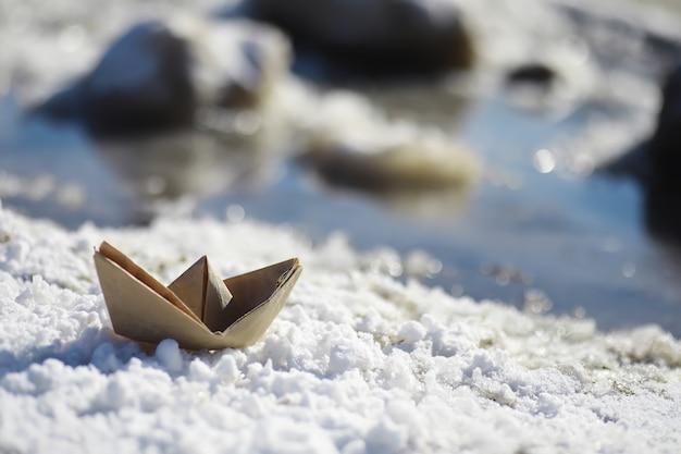 Papierowa łódź w wodzie na ulicy. pojęcie wczesnej wiosny. topniejący śnieg i łódź origami na falach.