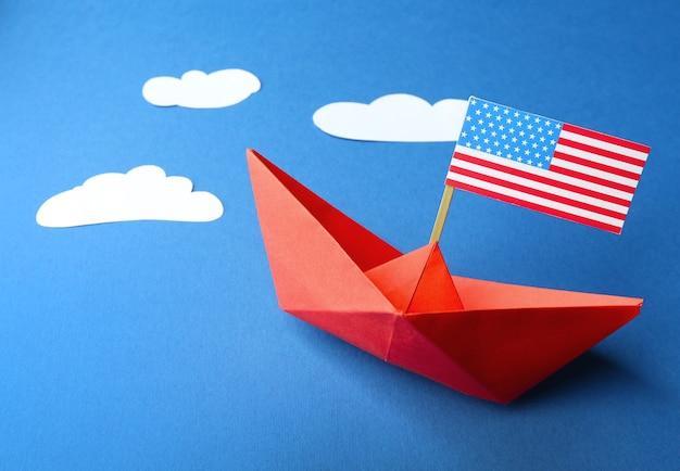 Papierowa łódź z amerykańską flagą. koncepcja szczęśliwy dzień kolumba