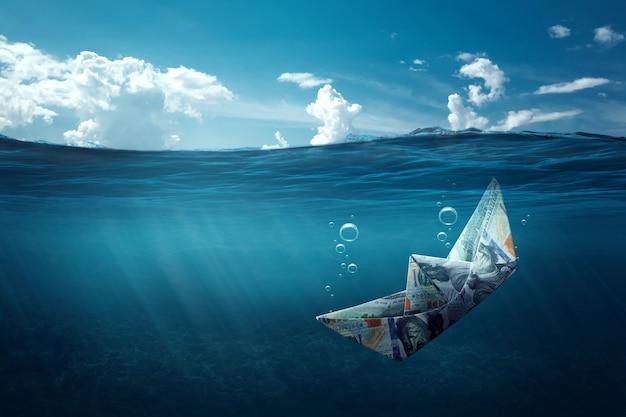 Papierowa łódź zrobiona z pieniędzy tonie w morzu pod wodą. koncepcja kryzysu finansowego, długi, płacenie rachunków, hipoteka, upadłość.