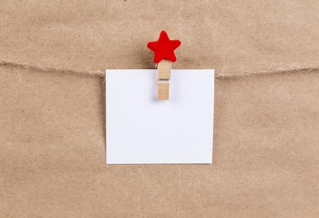 Papierowa naklejka wisząca na sznurze na drewnianej bielizny z czerwonego brokatu. świąteczne ozdoby. kartka świąteczna