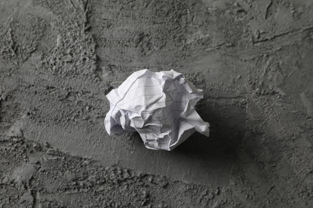 Papierowa piłka na szarym tle, przestrzeń dla teksta
