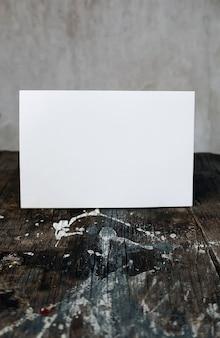 Papierowa pusta karta, pocztówka przy drewnianym stole z plamami farby, makieta listu vintage