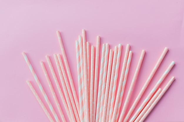 Papierowa słoma w pastelowych kolorach na różowo. wiele słomek koktajlowych w różowe paski