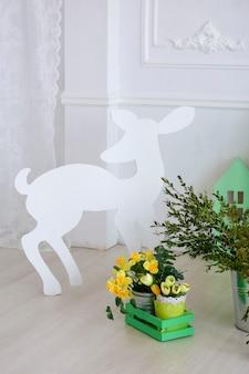 Papierowa sylwetka małego jelenia na tle wiosennych ozdób wielkanocnych, żółte kwiaty