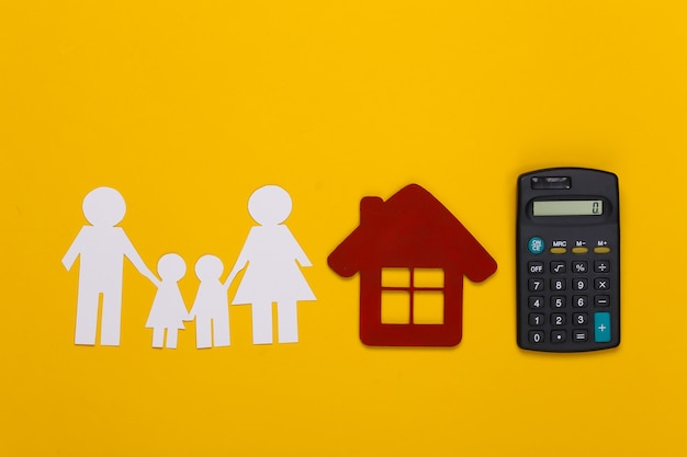 Papierowa szczęśliwa rodzina wraz z domem, kalkulator na żółto. kalkulacja wydatków rodzinnych, budżet