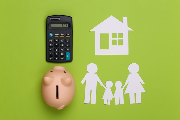 Papierowa szczęśliwa rodzina wraz z domem, skarbonką i kalkulatorem na zielono. budżet rodzinny