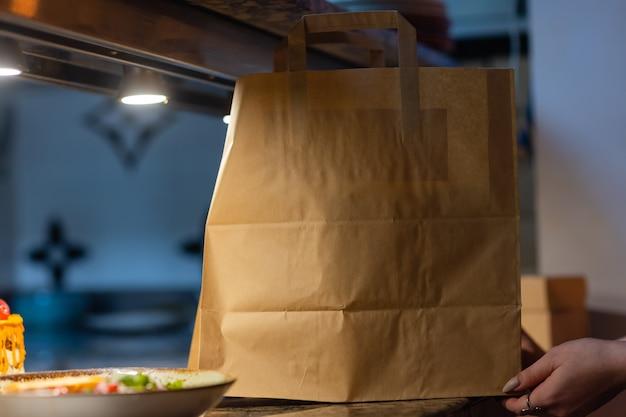 Papierowa torba deserowa czeka na klienta na ladzie w nowoczesnej kawiarni kawiarnia, dostawa żywności, kawiarnia, jedzenie na wynos.