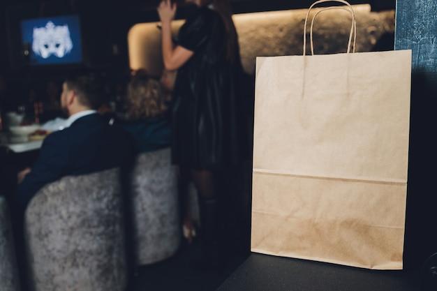 Papierowa torba deserowa czeka na klienta w restauracji w kawiarni, jedzenie na wynos, właściciel małej firmy.