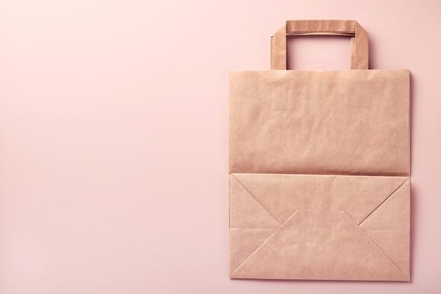 Papierowa torba, kubki, naczynia, drewniane widelce, słomki do picia, pojemniki na fast food, drewniane sztućce na różowym tle. zastawa stołowa z ekologicznego papieru rzemieślniczego. koncepcja recyklingu i dostawy żywności. makieta. widok z góry