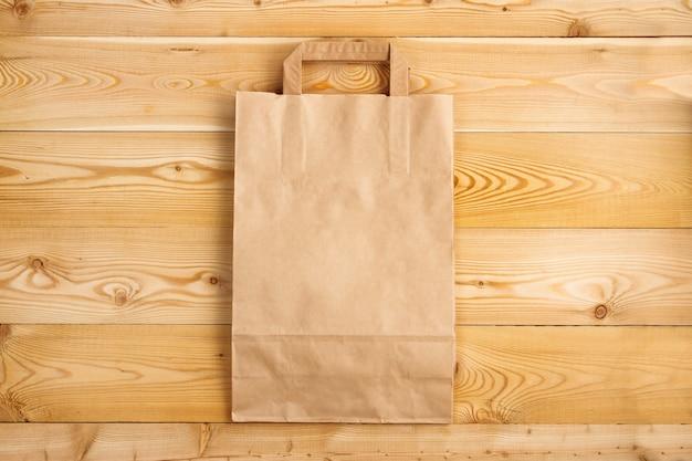 Papierowa torba na naturalnej drewnianej fakturze. jednorazowa torba papierowa na drewnianym tle
