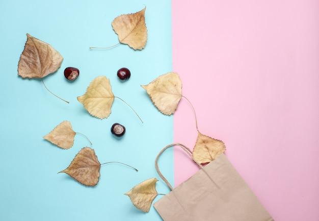 Papierowa torba na zakupy, opadłe jesienne liście, kasztany na niebieskim różowym stole. jesienne zakupy, sprzedaż, widok z góry, minimalizm