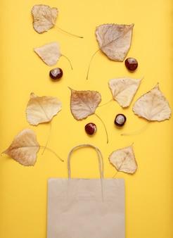 Papierowa torba na zakupy, opadłe jesienne liście, kasztany na żółtym stole. jesienne zakupy, sprzedaż, widok z góry, minimalizm