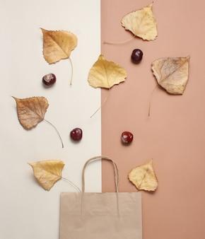 Papierowa torba na zakupy, opadłe jesienne liście na beżowo-brązowym stole. jesienne zakupy, sprzedaż, widok z góry, minimalizm