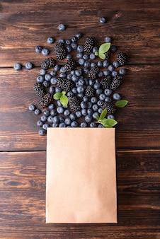Papierowa torba na zakupy z rozlewającymi się jagodami i jeżynami na ciemnym tle drewnianych, zdrowa żywność, letnie jagody.