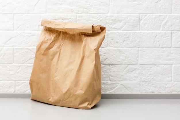 Papierowa torba pełno zdrowy jedzenie na drewnianym stole w kuchennym zakończeniu up z kopii przestrzenią