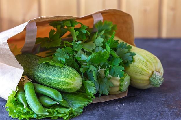 Papierowa torba różni zdrowi zieleni warzywa na zmroku stole. pojęcie właściwego odżywiania i zdrowej żywności. żywność ekologiczna i wegetariańska. widok z góry, leżał płasko, kopiować miejsca na tekst.