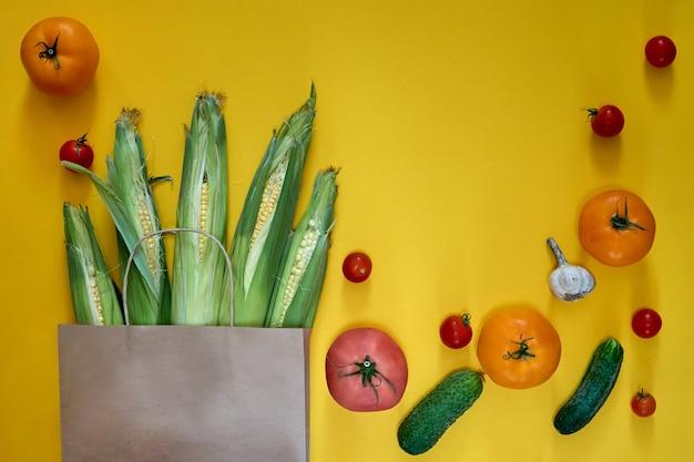 Papierowa torba rzemieślnicza z różnymi artykułami spożywczymi na żółtym tle. widok z góry pomidorki koktajlowe, ogórki, czosnek. sklep przy zbiorach kukurydzy, dostawa świeżych wegańskie zielone jedzenie.