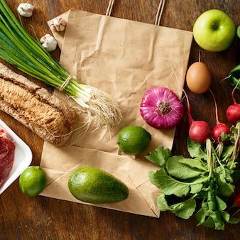 Papierowa torba ustawia zdrowego jedzenia drewnianego stołowego odgórnego widok