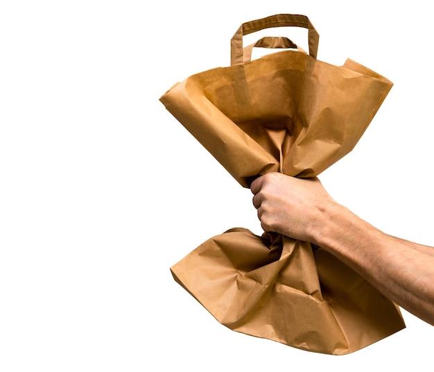 Papierowa torba w dłoni mężczyzny wyizolowana z białego tła