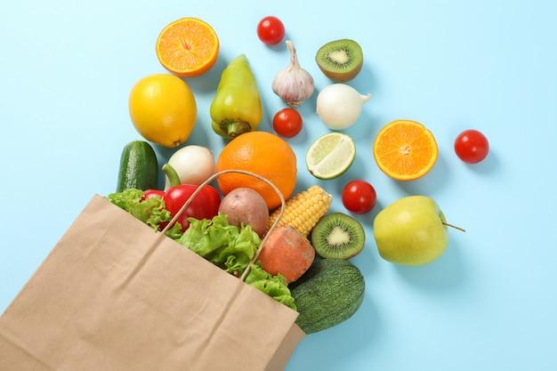 Papierowa torba, warzywa i owoc na błękit przestrzeni dla teksta