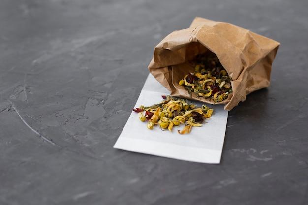 Papierowa torba wypełniona kolorowymi pąkami herbaty