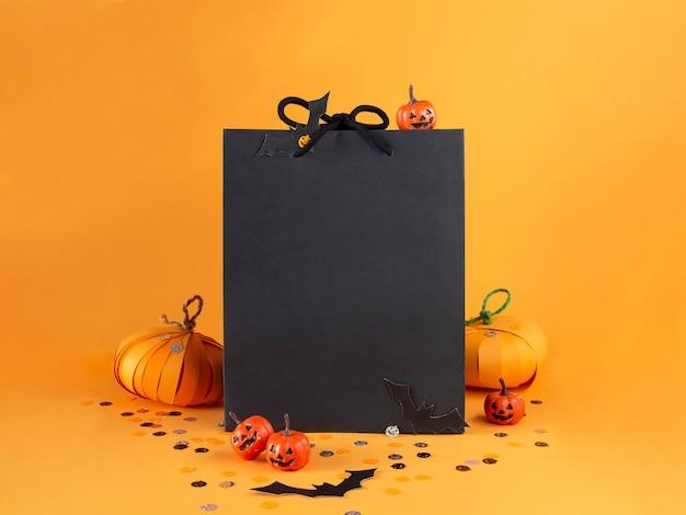 Papierowa torba z dekoracjami na halloween dynie nietoperze konfetti świąteczna koncepcja zakupów i sprzedaży